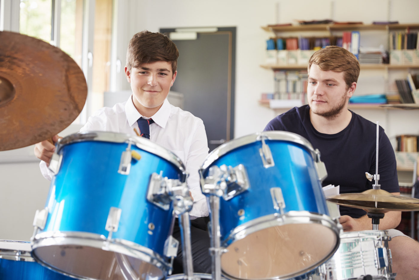 male-pupil-with-teacher-playing-drums-in-music-PJXEZDQ-2-e1541078668125.jpg