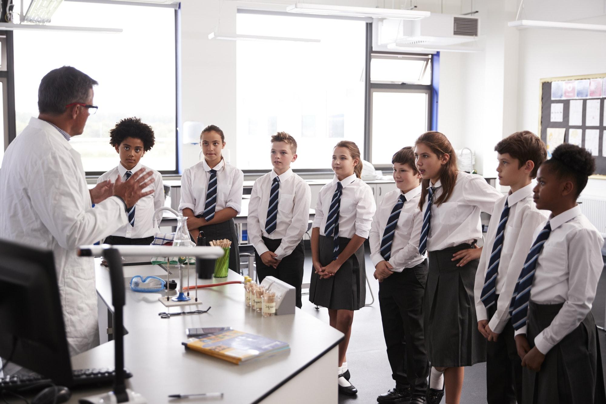 male-high-school-tutor-teaching-high-school-students-wearing-uniforms-in-science-class.jpg