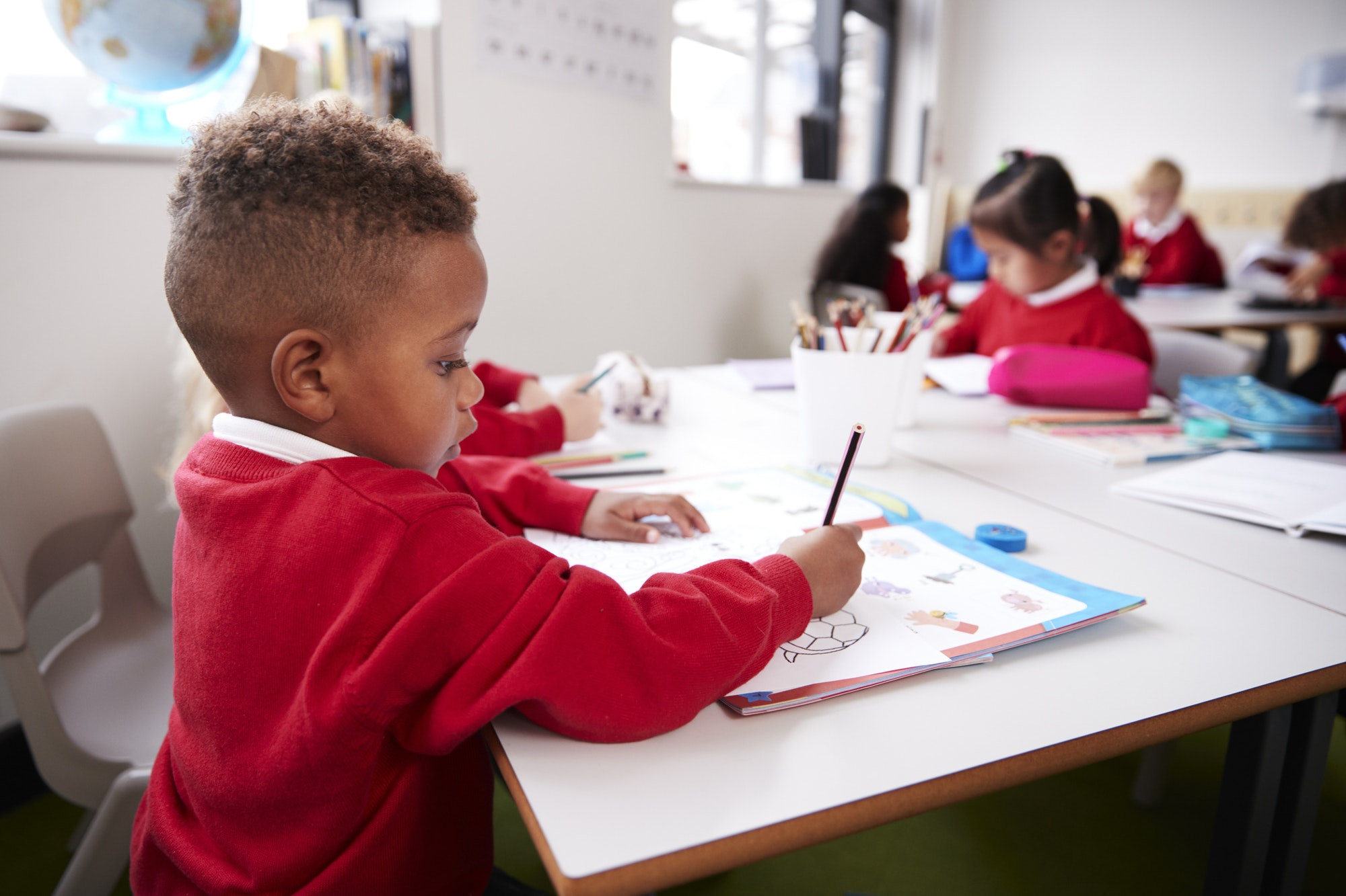 young-black-schoolboy-wearing-school-uniform-sitting-at-a-desk-in-an-infant-school-classroom-drawing-1.jpg