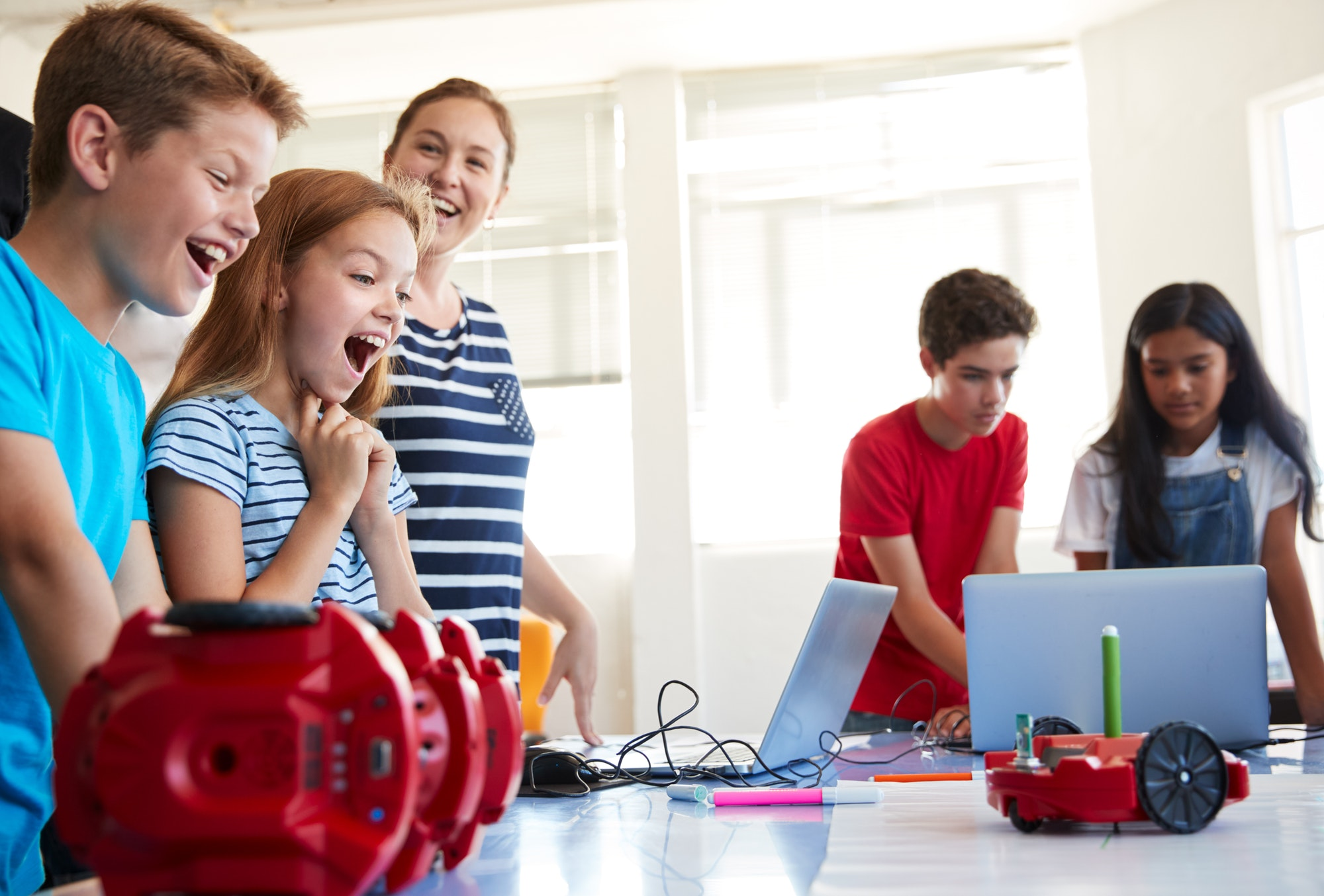 excited-students-watching-robot-vehicle-move-after-coding-lesson-in-computer-programing-class.jpg