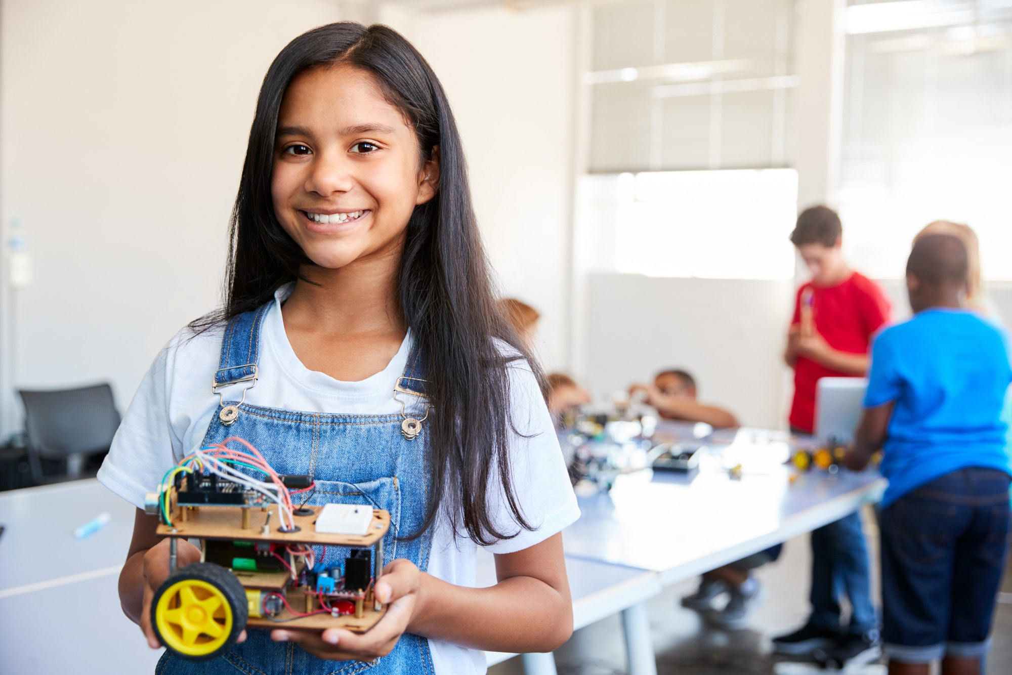 portrait-of-female-student-building-robot-vehicle-in-after-school-computer-coding-class-1.jpg