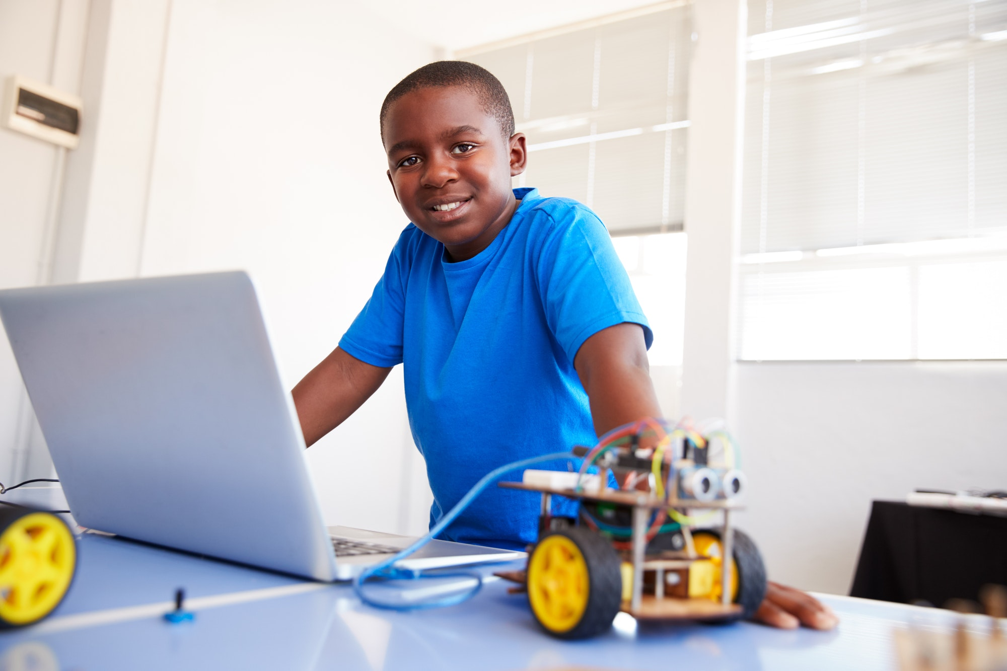 portrait-of-male-student-building-and-programing-robot-vehicle-in-school-computer-coding-class.jpg
