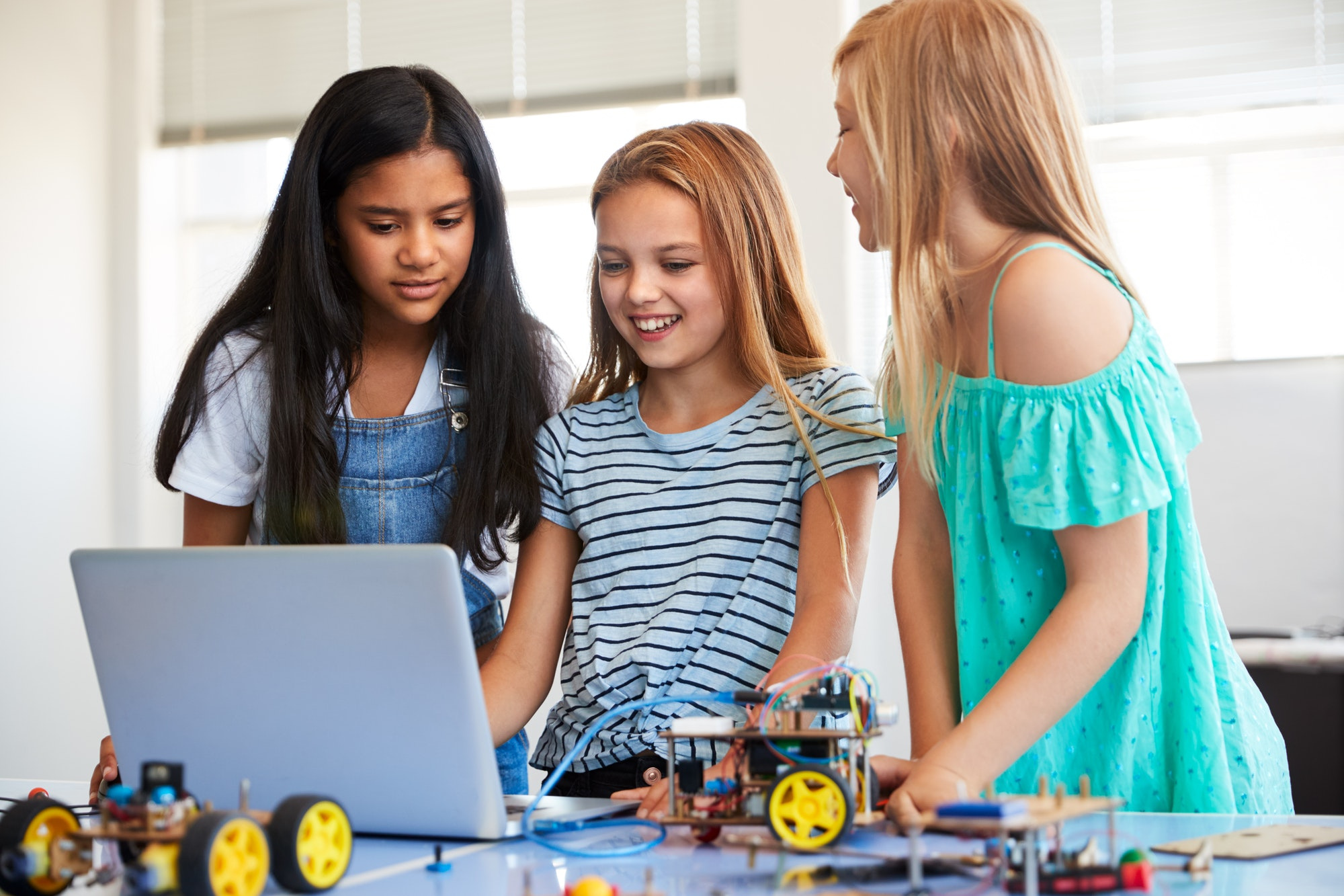 three-female-students-building-and-programing-robot-vehicle-in-after-school-computer-coding-class-1.jpg