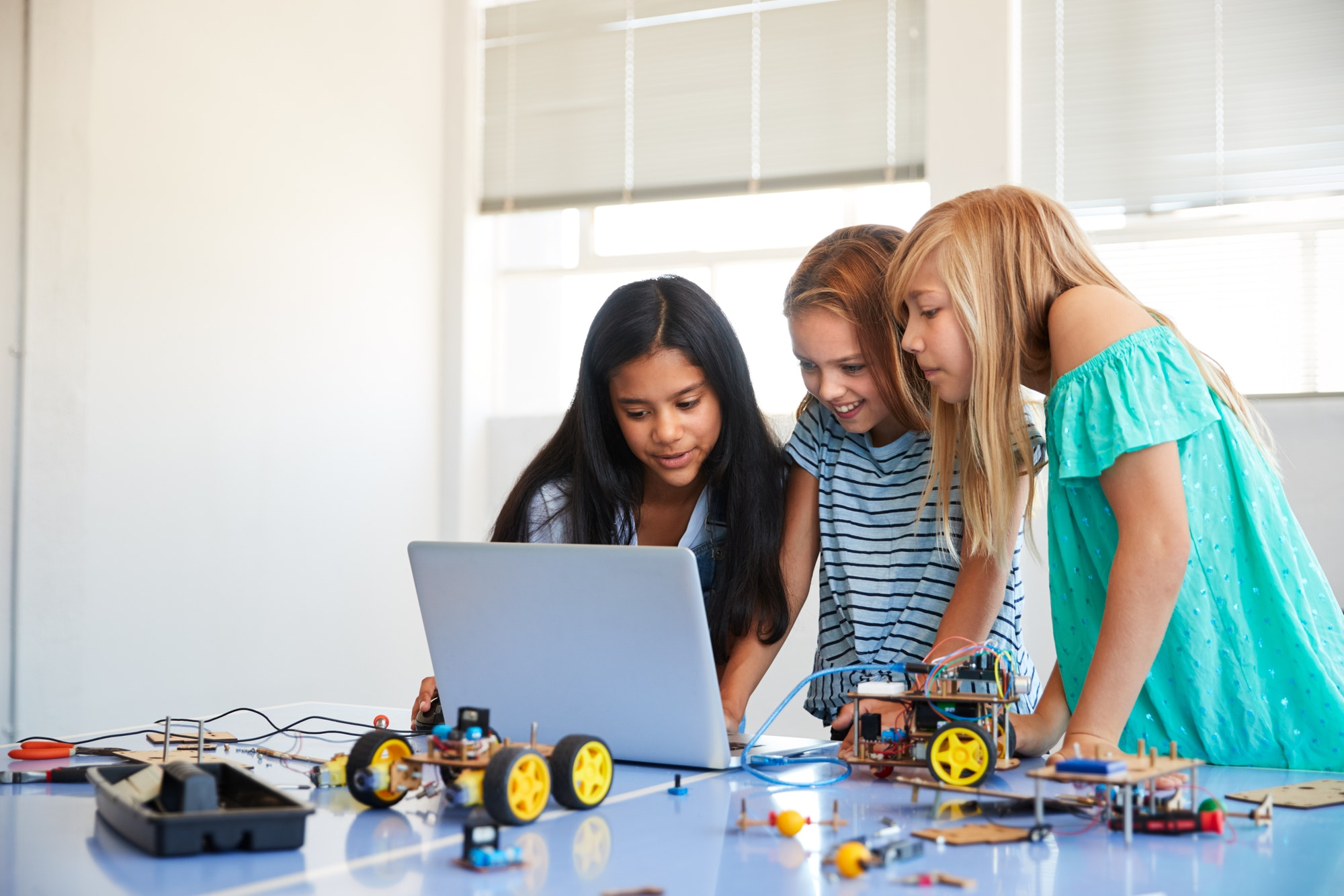 three-female-students-building-and-programing-robot-vehicle-in-after-school-computer-coding-class.jpg