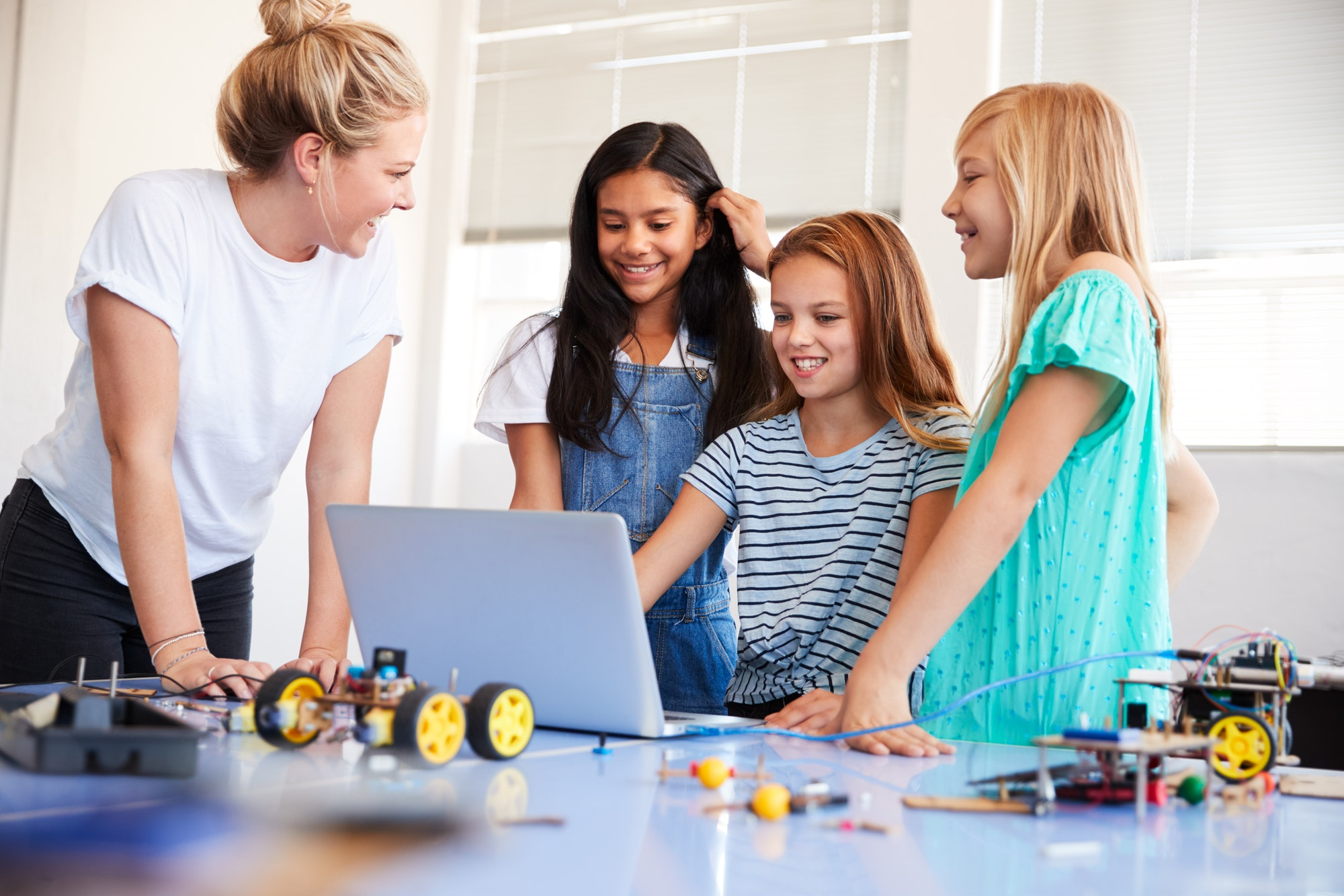 three-female-students-with-teacher-building-robot-vehicle-in-after-school-computer-coding-class-1.jpg