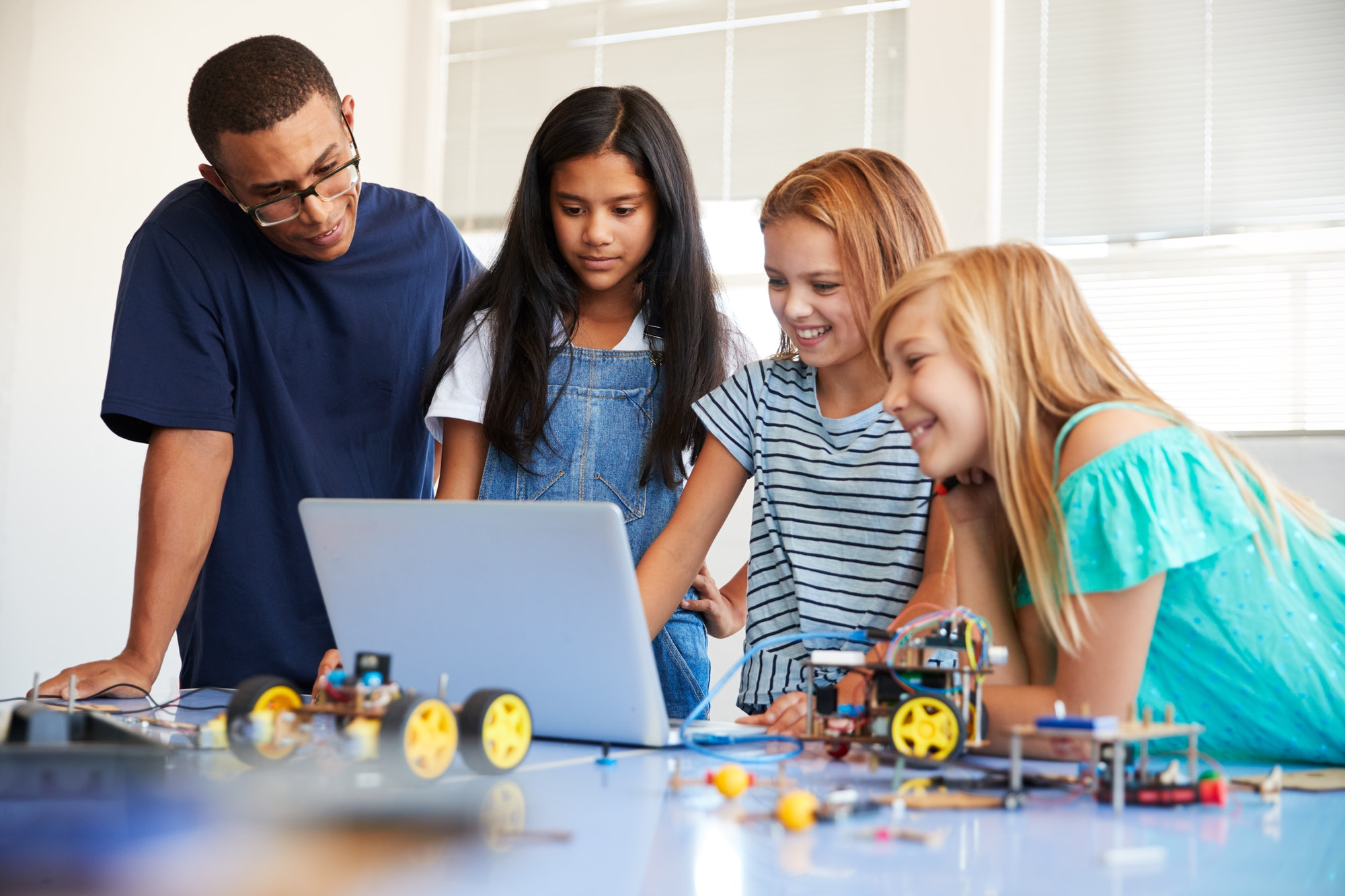 three-female-students-with-teacher-building-robot-vehicle-in-after-school-computer-coding-class.jpg