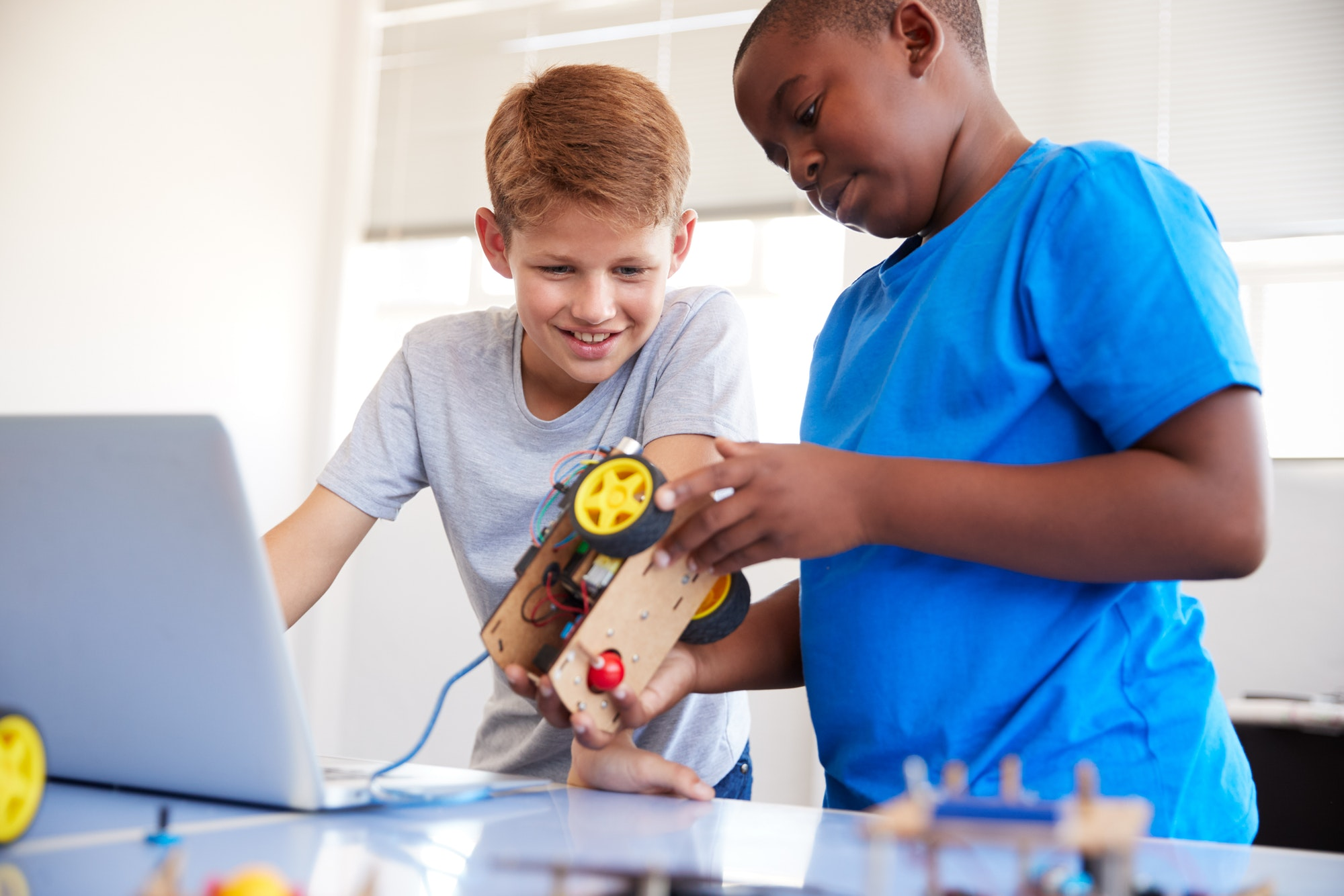 two-male-students-building-and-programing-robot-vehicle-in-after-school-computer-coding-class.jpg